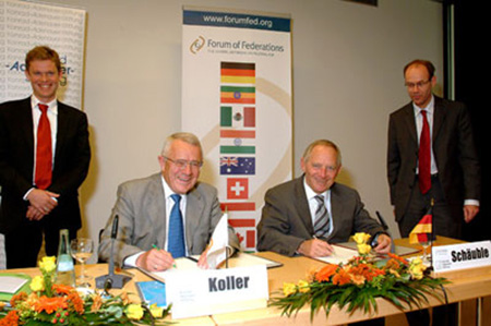 In Berlin, Forum Chairman Prof. Arnold Koller (left) and German Interior Minister Dr. Wolfgang Schäuble sign the partnership document between Germany and the Forum of Federations. The Forum's Felix Knüpling (top) and the Konrad Adenauer Foundation's Dr. Michael Borchard (right) witness the event.
